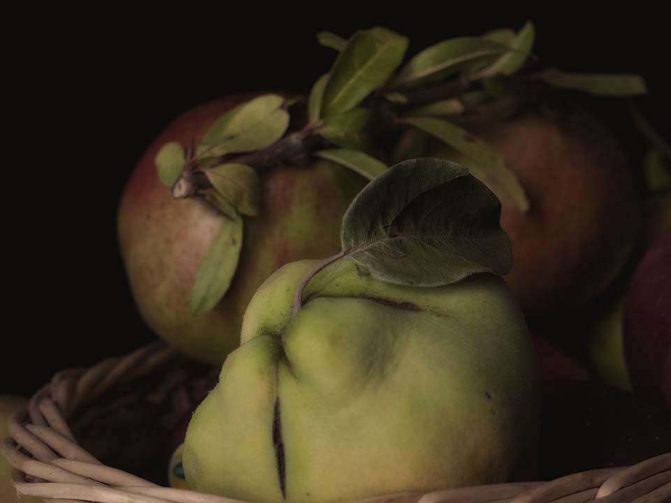 mela cotogna e melograno in un cesto